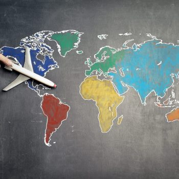 person-with-toy-airplane-on-world-map-3769138